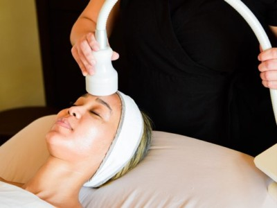 Woman receiving cryotherapy facial treatment