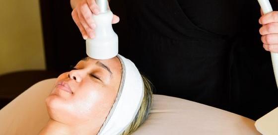 Woman receiving cryotherapy facial treatment