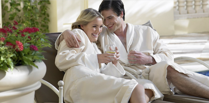 Couple in robes enjoying champagne at Acqualina