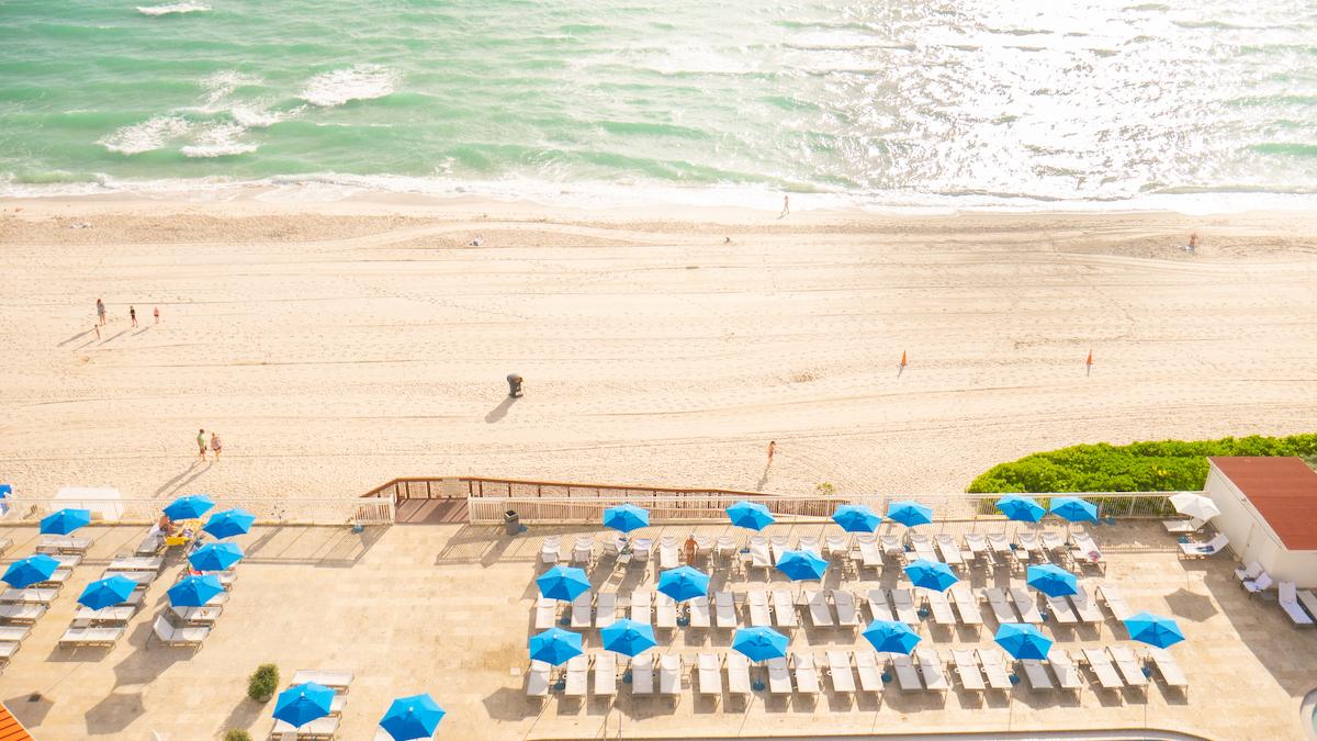 Glistening ocean water and white sand beach with blue umbrellas.