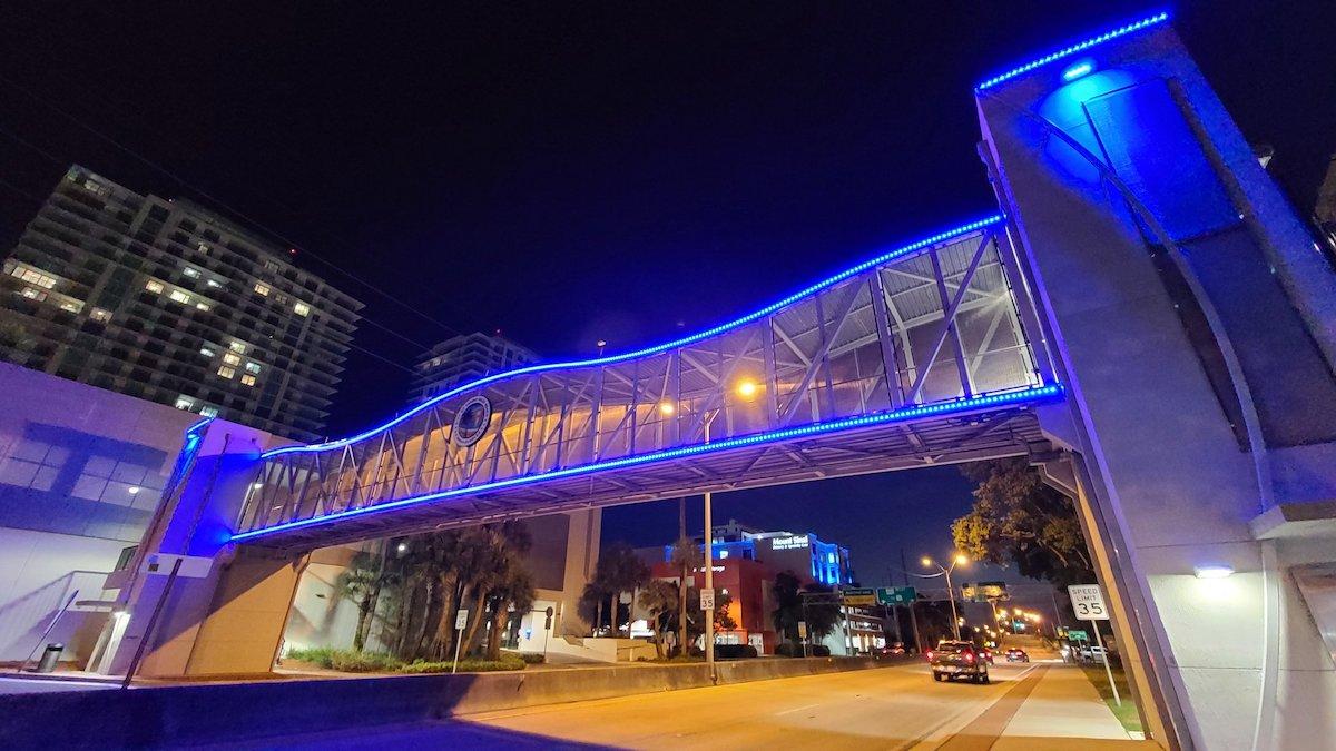 Pedestrian Bridge lite up at night over 163 Street.